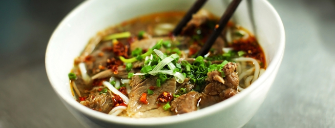 Chopsticks resting in a white bowl full of noodles, beef, herbs, and broth.