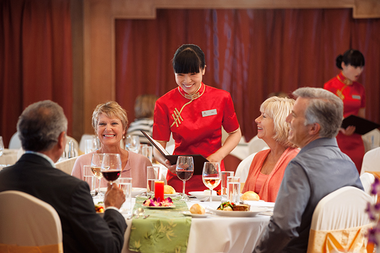 Restaurant server attending to smiling guests at a table
