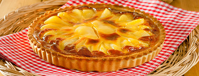A golden brown tart crust full of glazed pears and frangipane, placed on a red and white checked cloth.