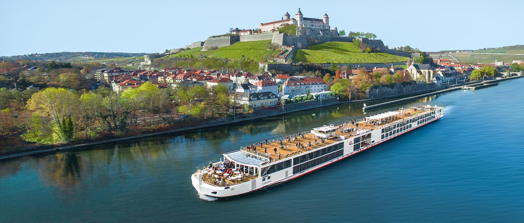A Viking river ship sailing past Marienberg Fortress on the Main river