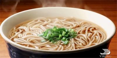 A steaming bowl of noodles in broth, with a small mountain of chopped chives in the center.