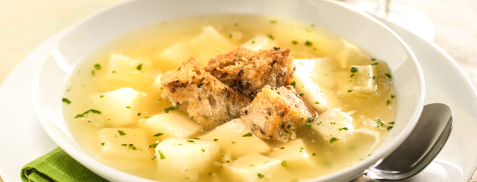 A pale soup full of potatoes and green herbs, topped with croutons and a serving spoon on the side.