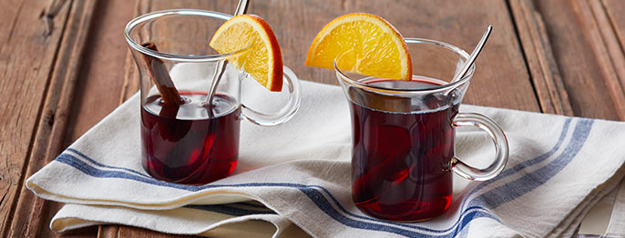 Two clear glass mugs of Gluhwein, a deep red liquid with cinnamon sticks and a orange slice sitting on top of a white tea towel.