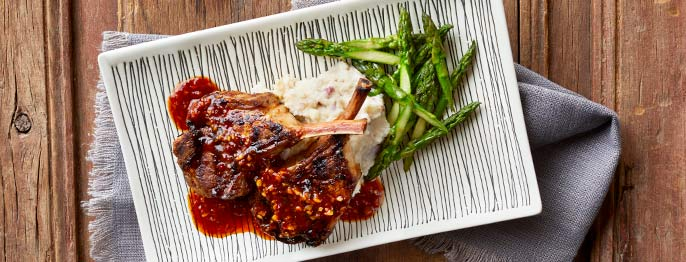 Lamb chops served with sauce on a decorative striped plate with asparagus and mashed potatoes.