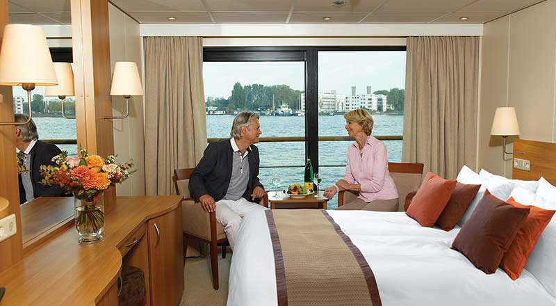 Two people sitting in a French Balcony stateroom on board a Viking river ship