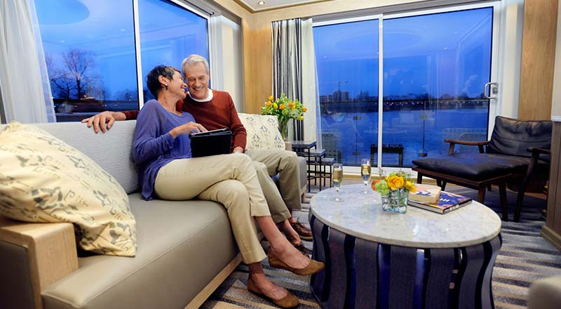 A couple sitting on a couch in a Viking River Ship Stateroom with the night-time city views out the window.