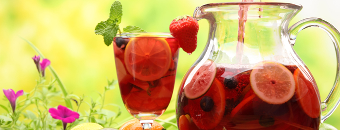 A pitcher of red liquid and sliced oranges, berries, and mint.
