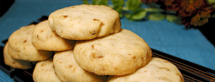 A stacked pyramid of shortbread cookies, studded with ginger and golden brown.