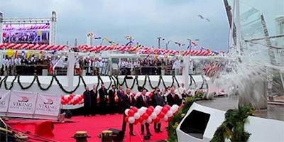 A celebration as a Christening happens for a Viking Ocean Ship with red and white balloons.